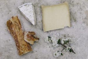 Fotografía artística con quesos, pan y decoración sobre tabla de mármol.