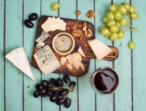 Vista desde arriba de tabla con uvas, frutos secos, miel y queso curado.