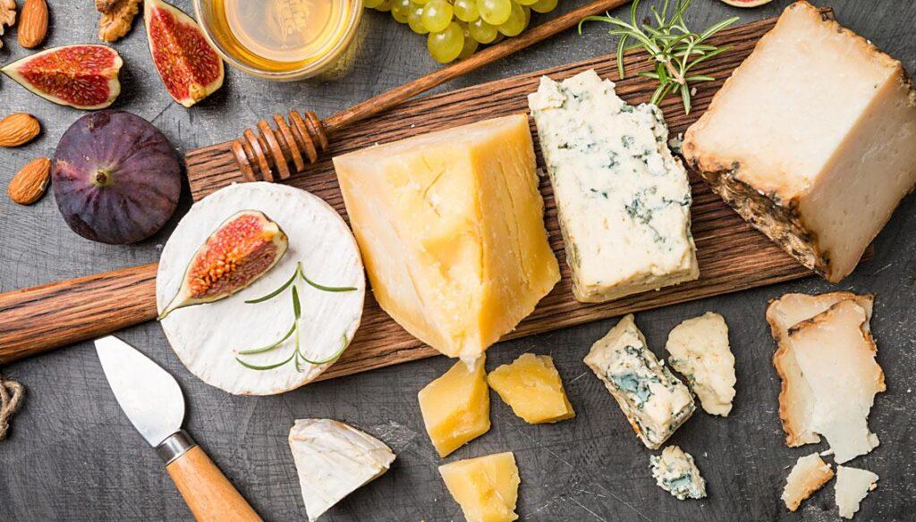 Tabla con quesos variados y fruta. Imagen para el artículo '10 curiosidades que todo amante del queso debería conocer'.